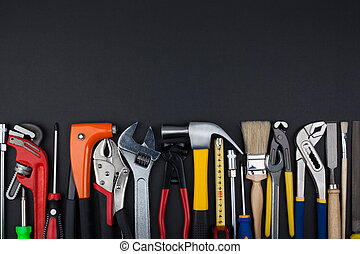 Work tools on black background. - Work tools lined up in a...