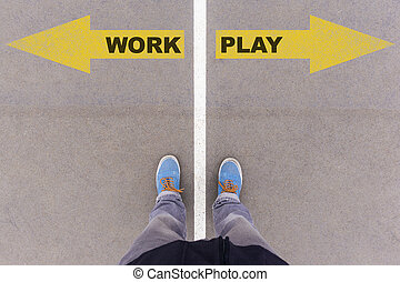 Work vs Play text on yellow arrows on asphalt ground, feet and shoes on floor, personal perspective footsie concept
