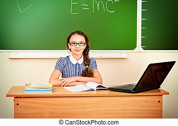 workbook - Modern schoolgirl sits at a desk during a lesson...