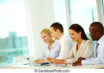 Four businesspeople sitting at table and working