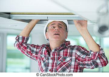 worke installing ceiling in building