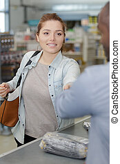 worker accepting payment from woman in hardware store