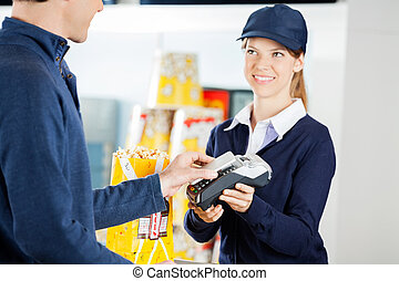 Worker Accepting Payment Through NFC Technology From Man In Cine