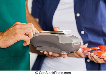 Worker Accepting Payment Through Smartphone In Store
