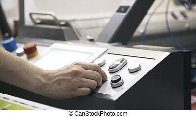 Worker adjusting print quality and pushing button
