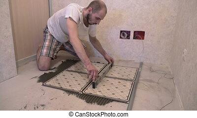 Worker aligns floor tiles on the floor - Worker aligns floor...