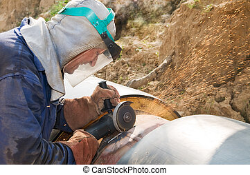 Builder works with circular abrasive cutoff saw grinding machine and sparkles at construction site