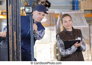 worker and manager distributing goods in a warehouse