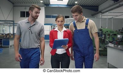 Worker and manager on factory floor discussing product specifications looking at a plan sheet
