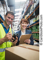 Worker and manager scanning package in warehouse - Portrait...