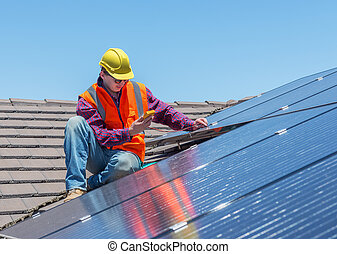 worker and solar panels - young worker checking solar panels...