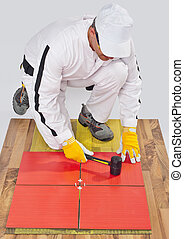 worker applies ceramic tiles on wooden floor with rubber hammer