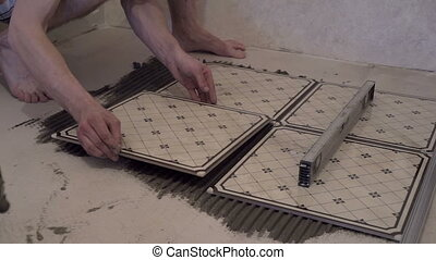 Worker applies glue for tiles on the floor