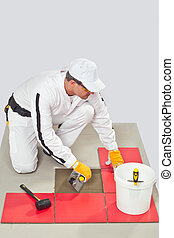Worker Applies Tile Adhesive with Notched Trowel on a Floor...