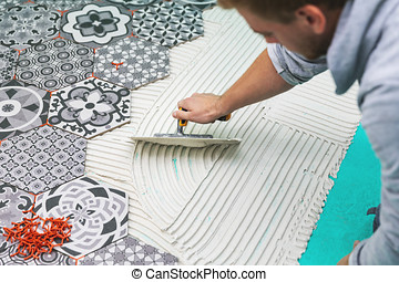worker applying tile adhesive on the floor