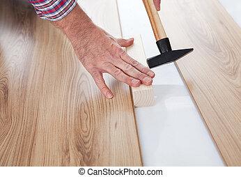 Worker assembling laminate floor using a hammer