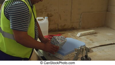 Worker assembling pieces of concrete block - Side view mid ...
