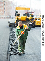 worker at asphalting works - Worker with shovel in front of...