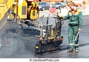worker at asphalting works - Worker operating asphalt paver...