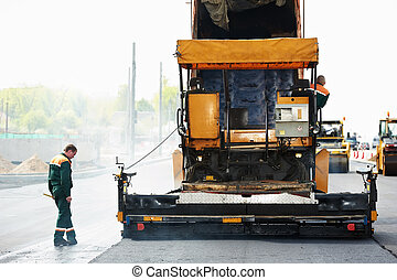 Worker operating asphalt paver machine during road construction and repairing works