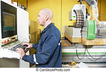 mechanical technician worker operating cnc milling machine center at wood furniture manufacture workshop