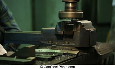 Worker at metal grinds workpiece on a horizontal milling machine.