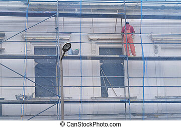 Worker at metal scaffolding