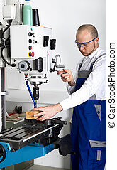 worker at milling machine - worker with safety glasses at...
