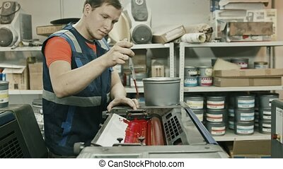 Worker at Polygraphy printing industry use Red paint on ink roller
