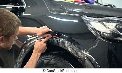 Worker at service station after the imposition of a vinyl film on the surface of body parts using a soft felt squeegee begins to smooth vinyl on the edges