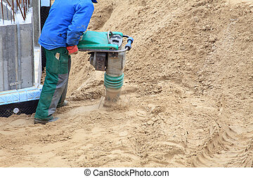 Worker at site working with compress tool
