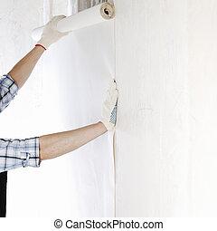 attaching wallpaper - worker attaching wallpaper to wall