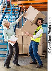Worker balancing heavy cardboard boxes