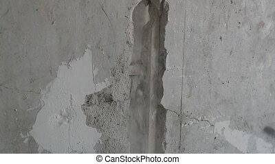 worker breaks the concrete wall with a large metal scrap.