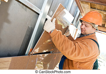 Worker builder at facade tile installation - One...