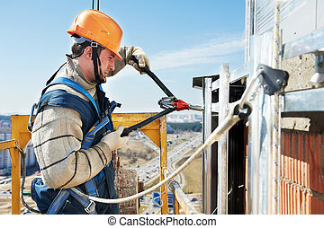 Worker builders at facade tile installation - worker builder...