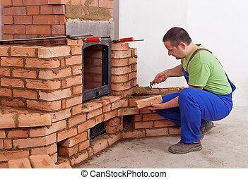 Worker building masonry heater