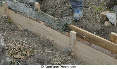 Worker building wall - Worker spreading concrete in formwork...