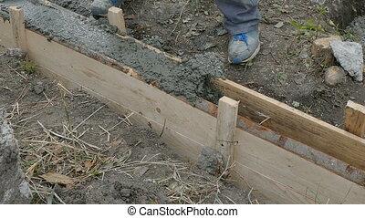 Worker building wall - Worker spreading concrete in formwork...