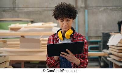 Worker busy with inventory in wood workshop using tablet...