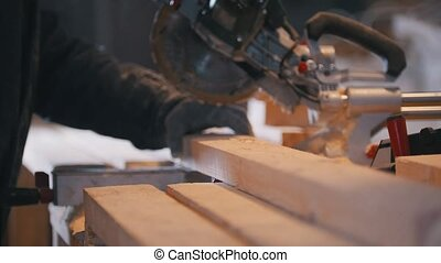 Worker carpenter circular saw sawing a wooden board on ...