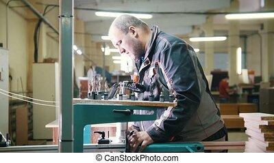 Worker carpenter cut a wooden fragment on a furniture...