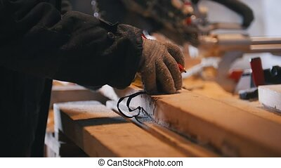 Worker carpenter figuring wooden board before circular saw...
