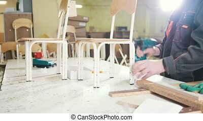 Worker carpenter is screwing chair leg with an electric...