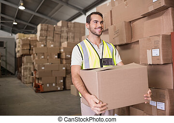 Worker carrying box in warehouse - Portrait of worker ...