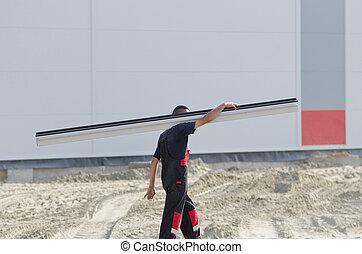 Worker carrying metal profile