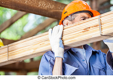 Worker Carrying Wooden Planks At Construction Site