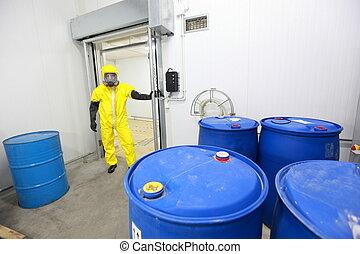 worker checking barrels - worker in protective uniform...