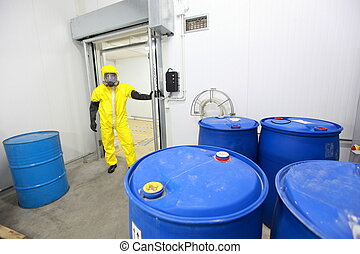 worker in protective uniform checking barrels with toxic subsatnce in plant