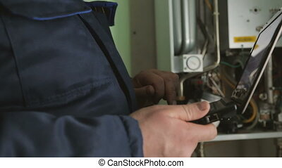 Worker checking gas-fire boiler